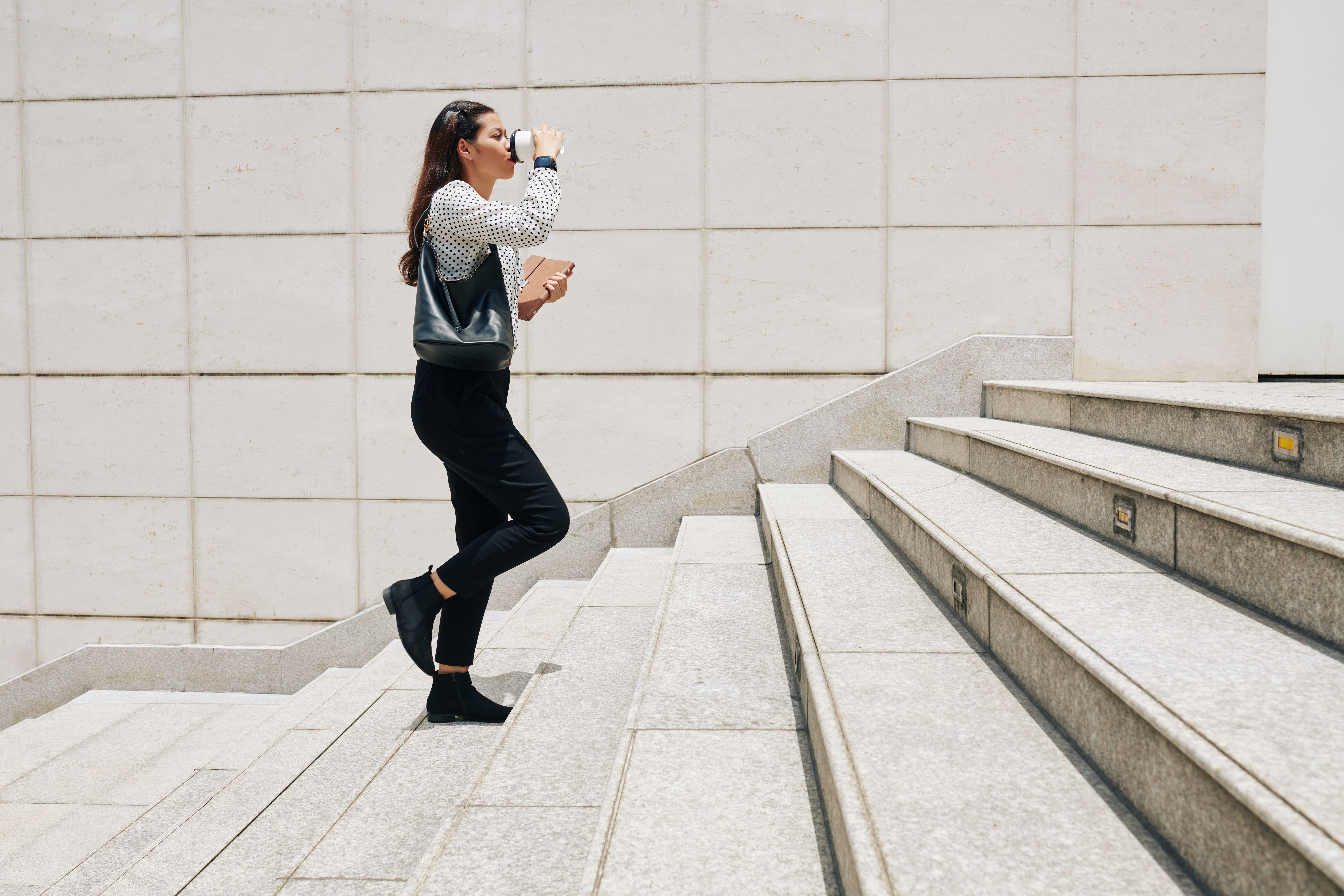 female-entrepreneur-walking-up-the-stairs-4EH8JCY