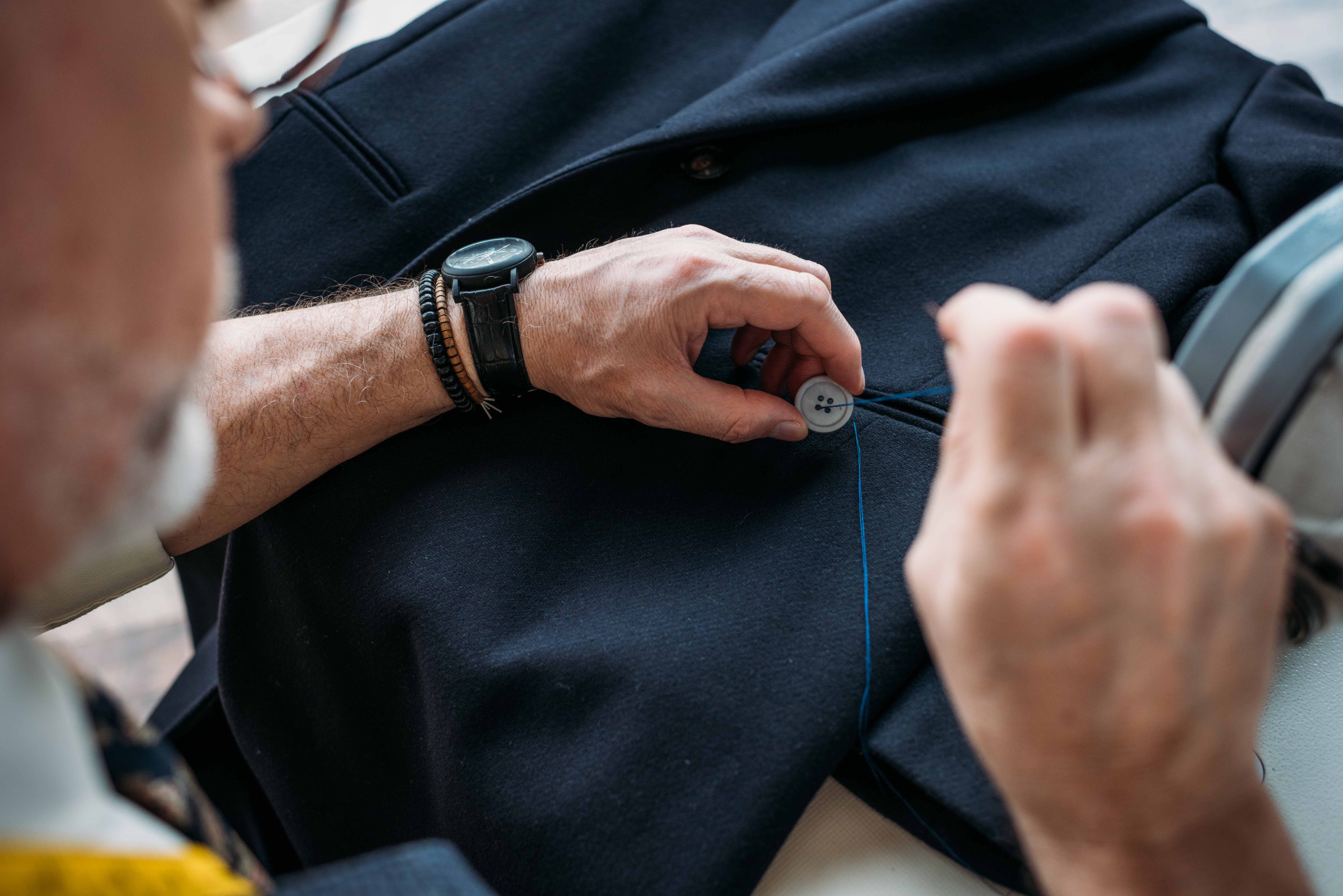 cropped-image-of-tailor-sewing-button-to-jacket-at-F3N23FE